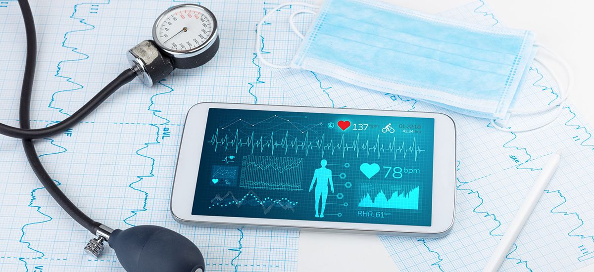 Image of a  blood pressure measuring device and a smartphone showing  vital signs on a background of a face mask and heart trace print-outs
